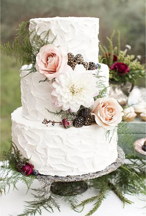 Buttercream Wedding Cake With Decorative Florals and Pinecones