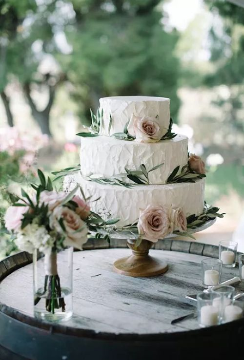 Three-Tiered White Wedding Cake With Flowers and Greenery