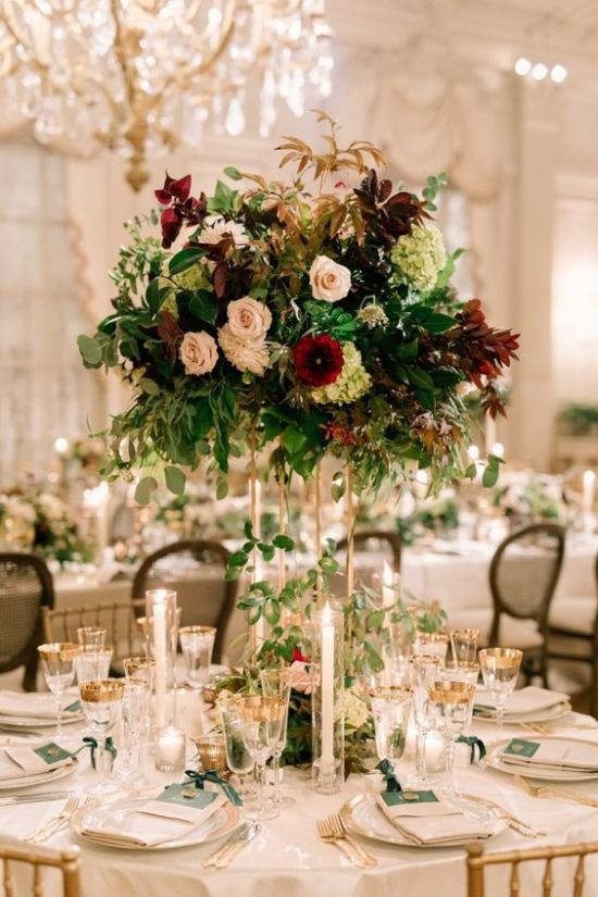 A Bold And Lush Floral Wedding Centerpiece In Blush Burgundy And Green Blooms And Foliage Of Various Shades