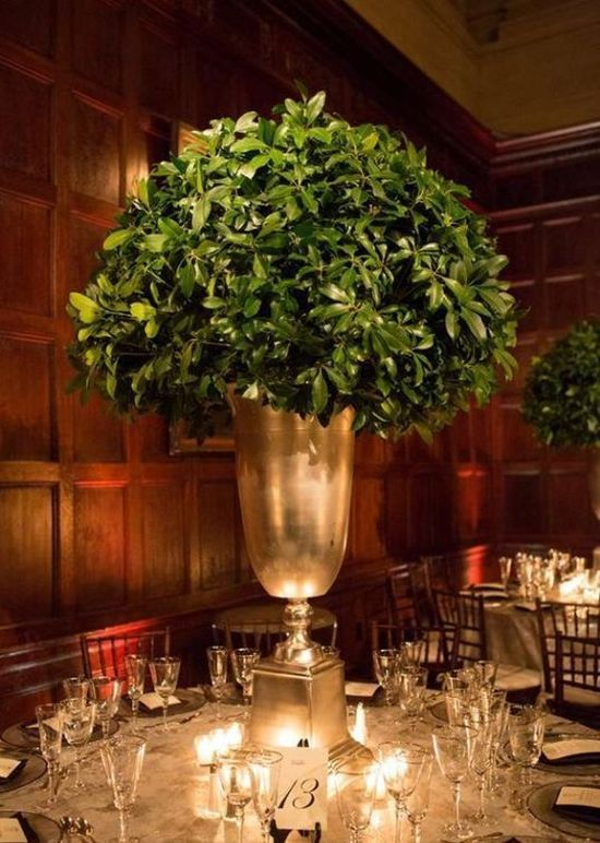 An Elegant Winter Wedding Centerpiece Of A Metallic Urn With Much Greenery In It