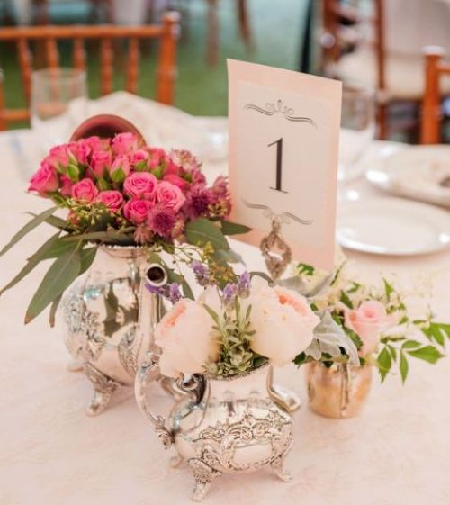 Bright And Fun Centerpiece Of A Silver Teapot And Coffee Pit Used As Vases For Blush And Hot Pink Blooms And A Table Number