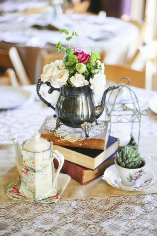 Catchy Vintage Centerpiece Of A Stack Of Books Plus A Silver Teapot With Blooms With A Potted Succulent And A Cage And A Coffee Pot