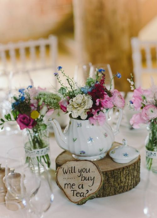Cool Teapot Wedding Centerpiece Of A Wood Slice A Wood Sign A Floral Teapot With Bright Blooms Glasses And Bright Flowers