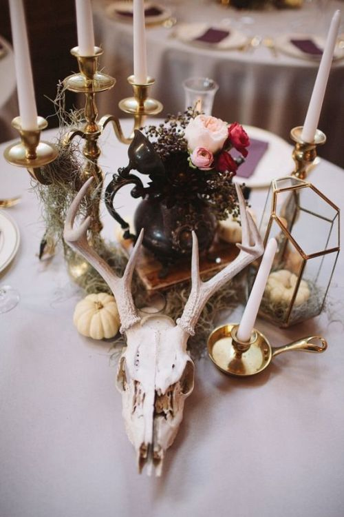Eclectic Wedding Centerpiece Of A Skull Plus Pumpkins And Candles With A Black Teapot And Bright Blooms