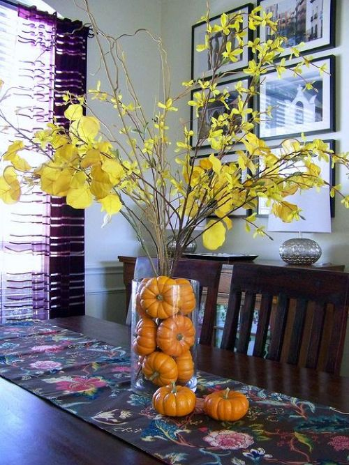 Fall Wedding Décor Idea With A Clear Vase Filled With Orange Pumpkins And Branches With Yellow Leaves