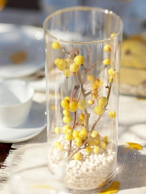 Fall Wedding Décor Idea With A Clear Vase Filled With White Beads And With Branches With Yellow Berries Inside