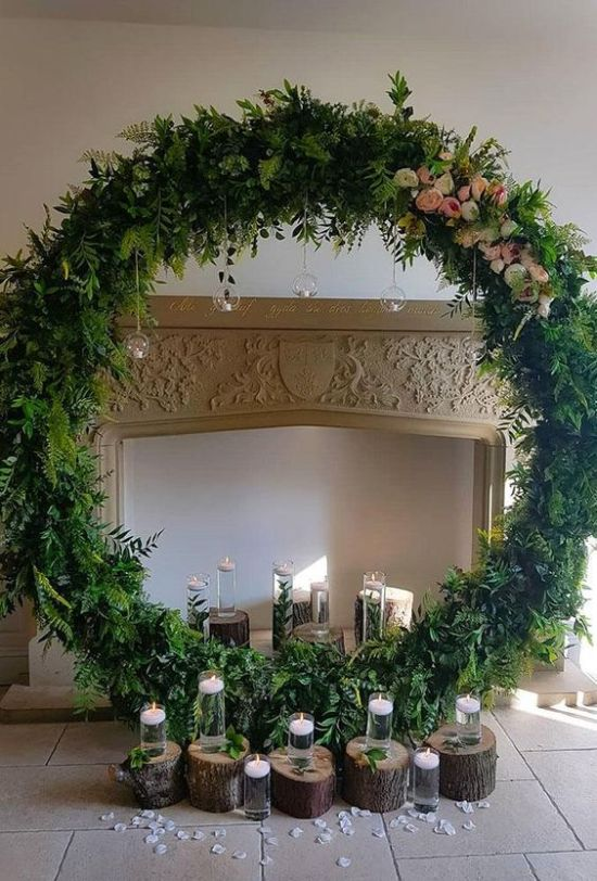 Greenery Round Wedding Altar With Blooms And Candles On Stumps And Hanging Down From The Wreath