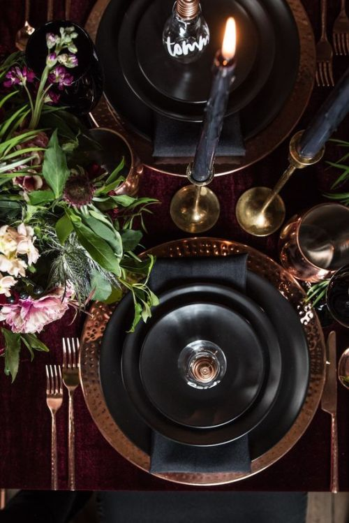 Halloween Table Setting With A Burgundy Tablecloth Plus Metallic Hammered Chargers And Black Candles Plus A Chic Floral Centerpiece