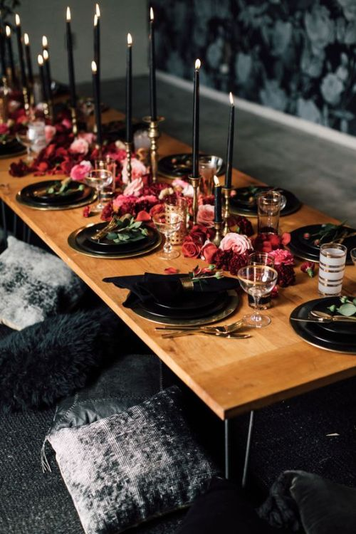 Halloween Wedding Table Setting Ideas With A Chic Moody Tablescape With Black Plates And Chargers Plus Black Candles And Lush Red And Pink Blooms Right On The Table