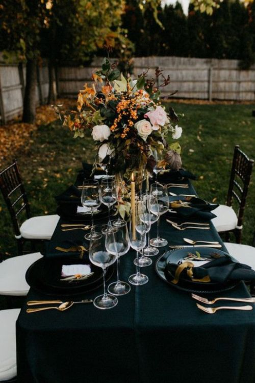 Halloween Wedding Table Setting Ideas With A Chic Tablescape With A Black Tablecloth And Napkins Plus Gilded Touches And A Lush Floral Centerpiece With Berries