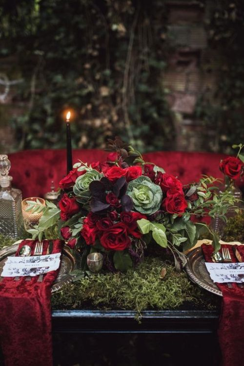 Halloween Wedding Table Setting Ideas With A Dark Romance Tablescape With A Moss Table Runner Plus Red Napkins And Black Candles And A Lush Wedding Centerpiece With Veggies