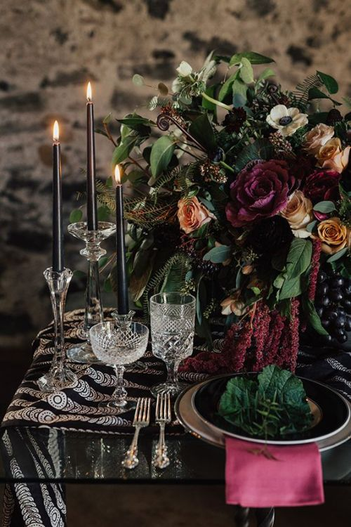 Halloween Wedding Table Setting Ideas With A Dark Wedding Table Setting With Black Candles And A Black Printed Table Runner Plus A Pink Napkin And A Lush Floral Centerpiece And Greenery