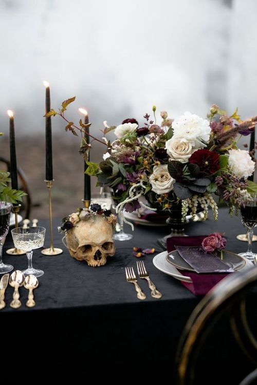 Halloween Wedding Table Setting Ideas With A Decadent Halloween Tablescape With Moody Florals And A Black Tablecloth And Candles Plus Elegant Silver Cutlery And Grey Plates