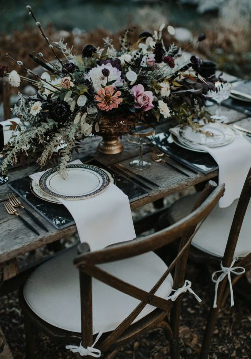 Halloween Wedding Table Setting Ideas With A Gorgeous Haunted Tablescape With A Lush Textural Centerpiece Plus Marble Chargers And Printed Plates Plus Gilded Touches And White Napkins
