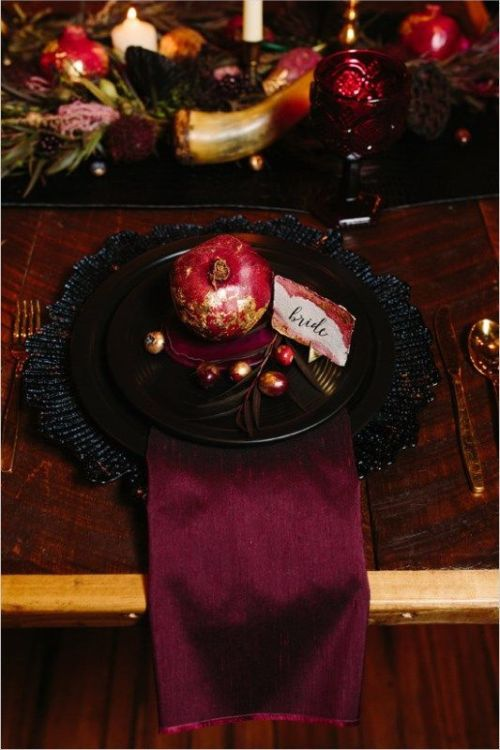 Halloween Wedding Table Setting Ideas With A Place Setting Styled With A Plum-Colored Napkin And Black Chargers And Plates Plus Pomegranates And A Colored Glass
