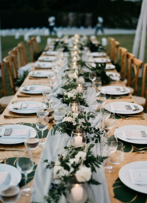 Long Table Spruced Up With An Airy Grey Table Runner And Candles In Glass Candle Holders And Lush Greenery And White Blooms