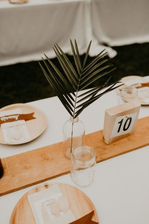 Minimalist Wedding Centerpiece Idea With A Bottle With A Single Tropical Leaf