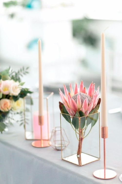 Minimalist Wedding Centerpiece Idea With A Single King Protea Inserted Into A Geometric Candle Holder And Some Candles In Taller Candle Holders