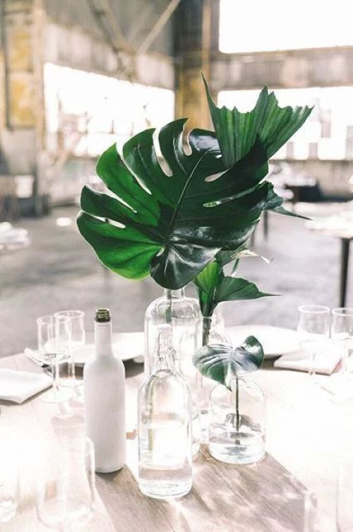 Minimalist Wedding Centerpiece Idea With An Arrangement Of Clear Vases With A Single Tropical Leaf In Each For A Minimalist Tropical Wedding