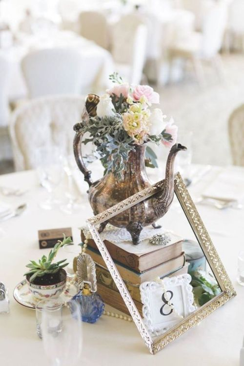 Unique Wedding Centerpiece Of A Stack Of Books Plus A Frame Plus A Silver Teapot With Blush Blooms With Succulents And A Table Number