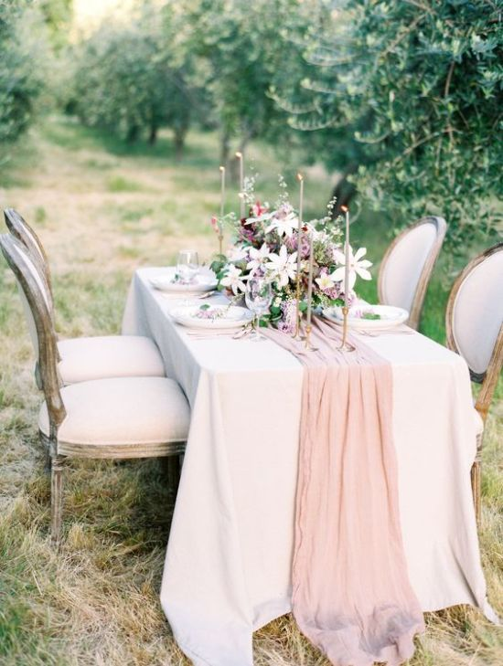 A Blush Silk Table Runner And Matching Candles For Adding Elegance To The Table