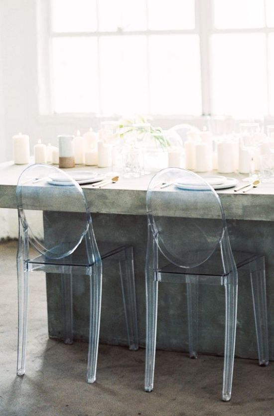 A Concrete Wedding Dining Table With Lots Of Candles And Acrylic Chairs