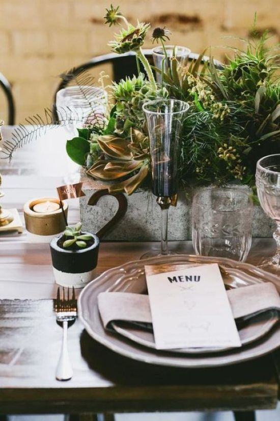 A Large Concrete Wedding Planter With Various Textural Greenery And Foliage And A Metallic Table Number