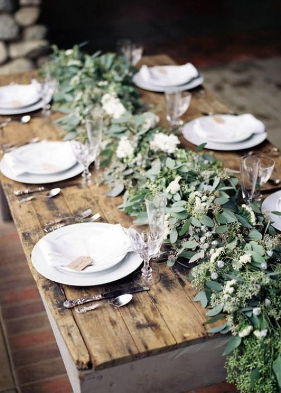 A Very Lush Greenery Table Runner With Berries And White Blooms Over A Naked Table