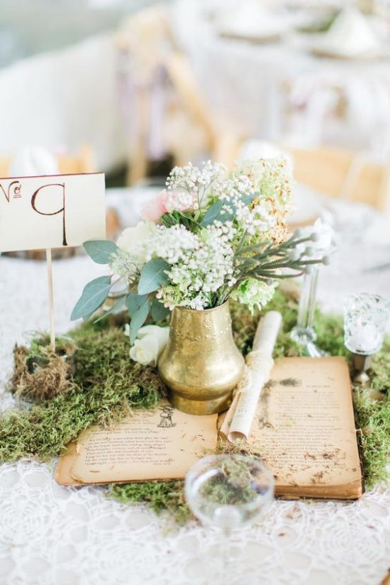 Chic Vintage-Inspired Wedding Centerpiece Idea With Moss And An Open Book Plus A Gilded Vase And Blooms Plus A Table Number
