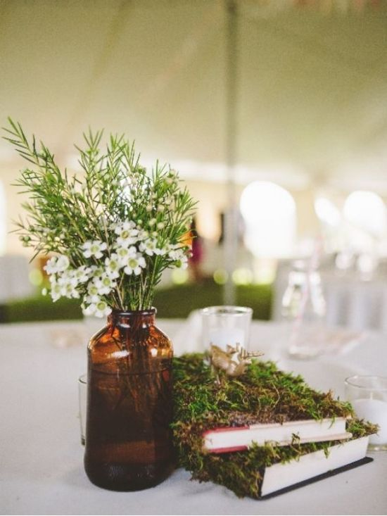 Simple And Rustic Wedding Centerpiece Idea With Moss Covered Books And An Amber Glass Vase Plus Wildflowers And Greenery