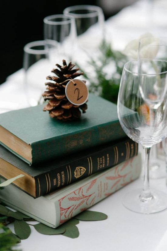 Winter Wedding Centerpiece Idea With A Stack Of Vintage Books And A Pinecone With A Table Number Tag