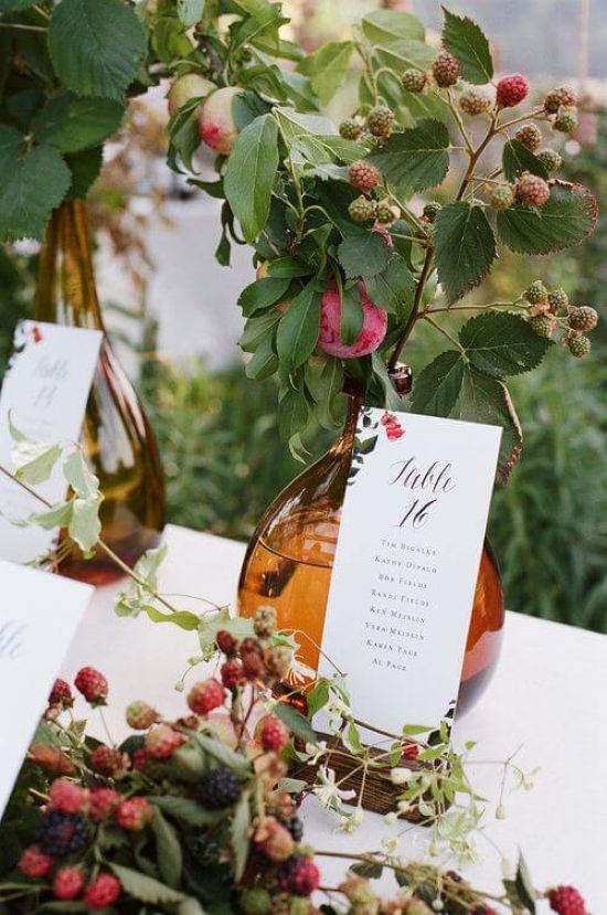 Wedding Seating Plan Idea With Bottles Filled With Berries And Vines